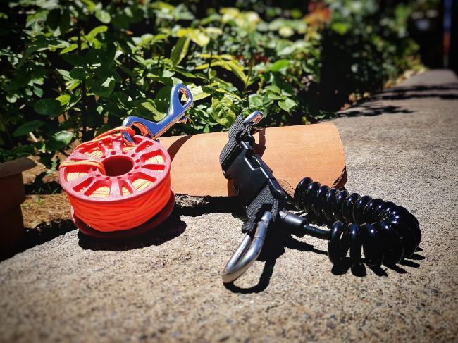Carrete y mosquetón en el equipamiento de buceador